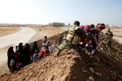 Soldati curdi aiutano la popolazione di Mosul a fuggire verso nord (Thomas Van Linge/Twitter).
