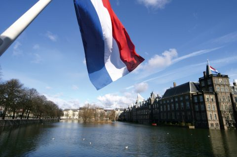 Dutch flag with the parliament buildings in the background; The Hague, Netherlands